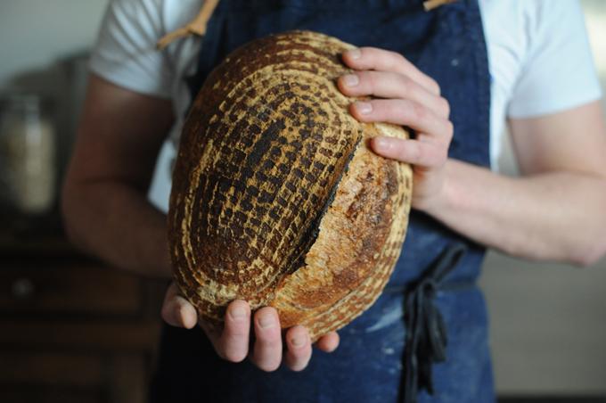 male baker holding patterned loaf
